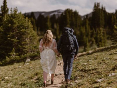 A bride, in a white dress, and a groom, wearing a blue suit and backpack, walk down a rocky path towards a forest of green trees.