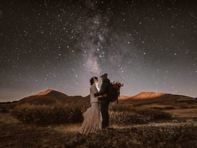 A man and a woman stand in a field with the starry night sky lit up above them.