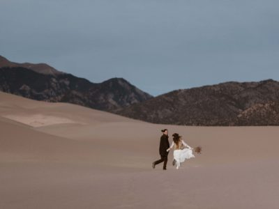 A couples running through the Great Sand Dunes National Park