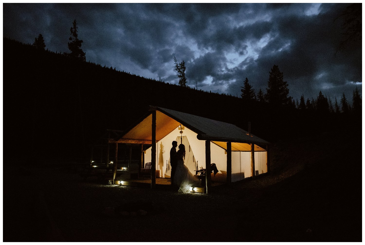 A bride and groom embrace underneath a tent in the dark.
