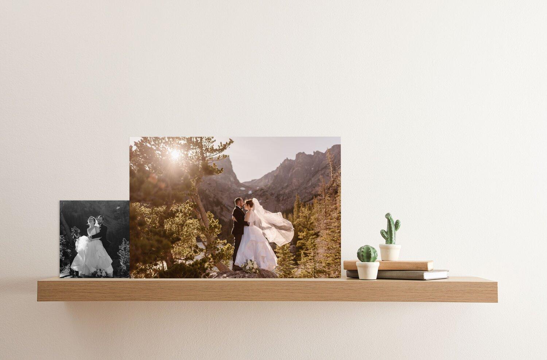 Two wedding photos sitting on a shelf.