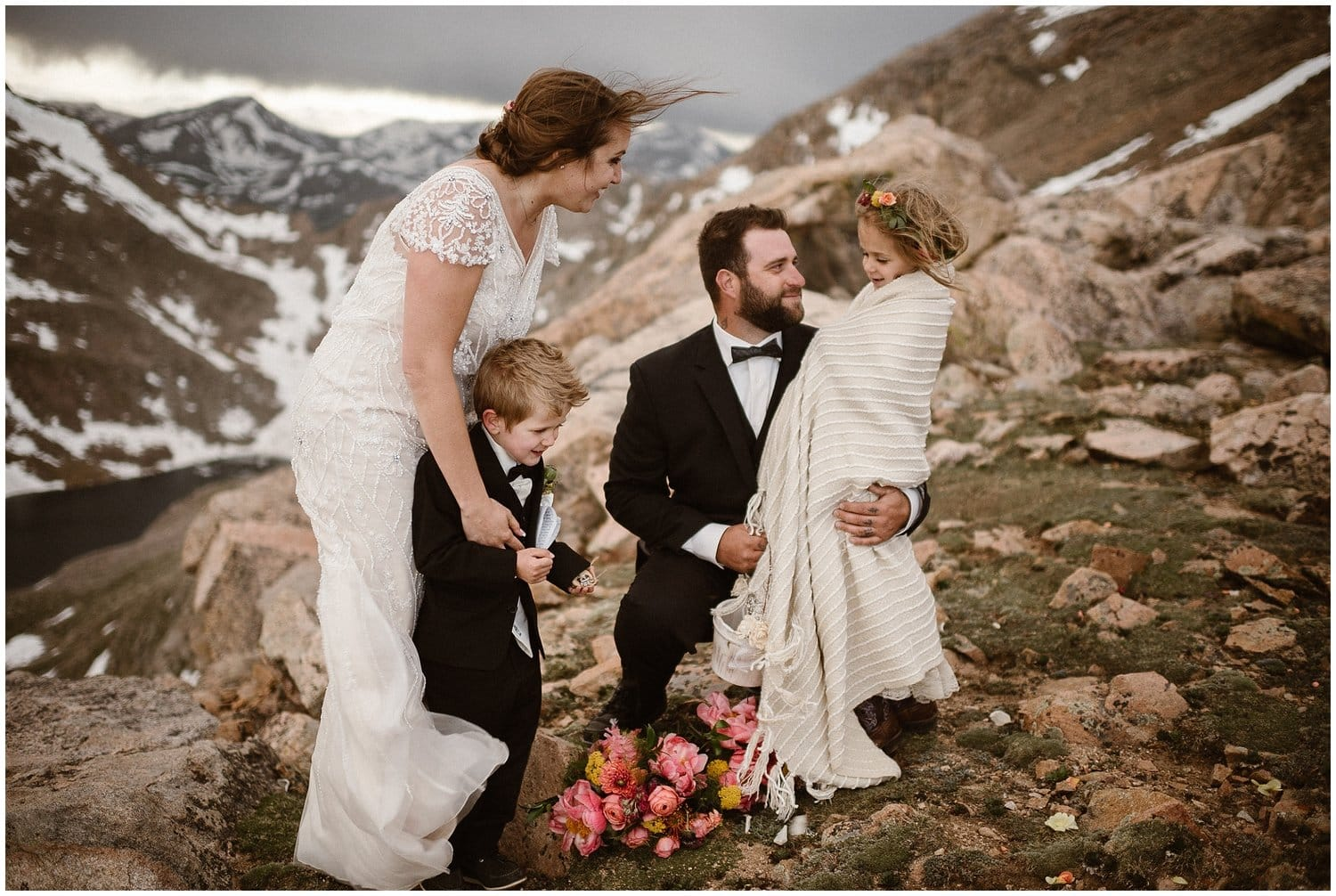 A bride and groom smile at each other while embracing their two kids in the mountains.