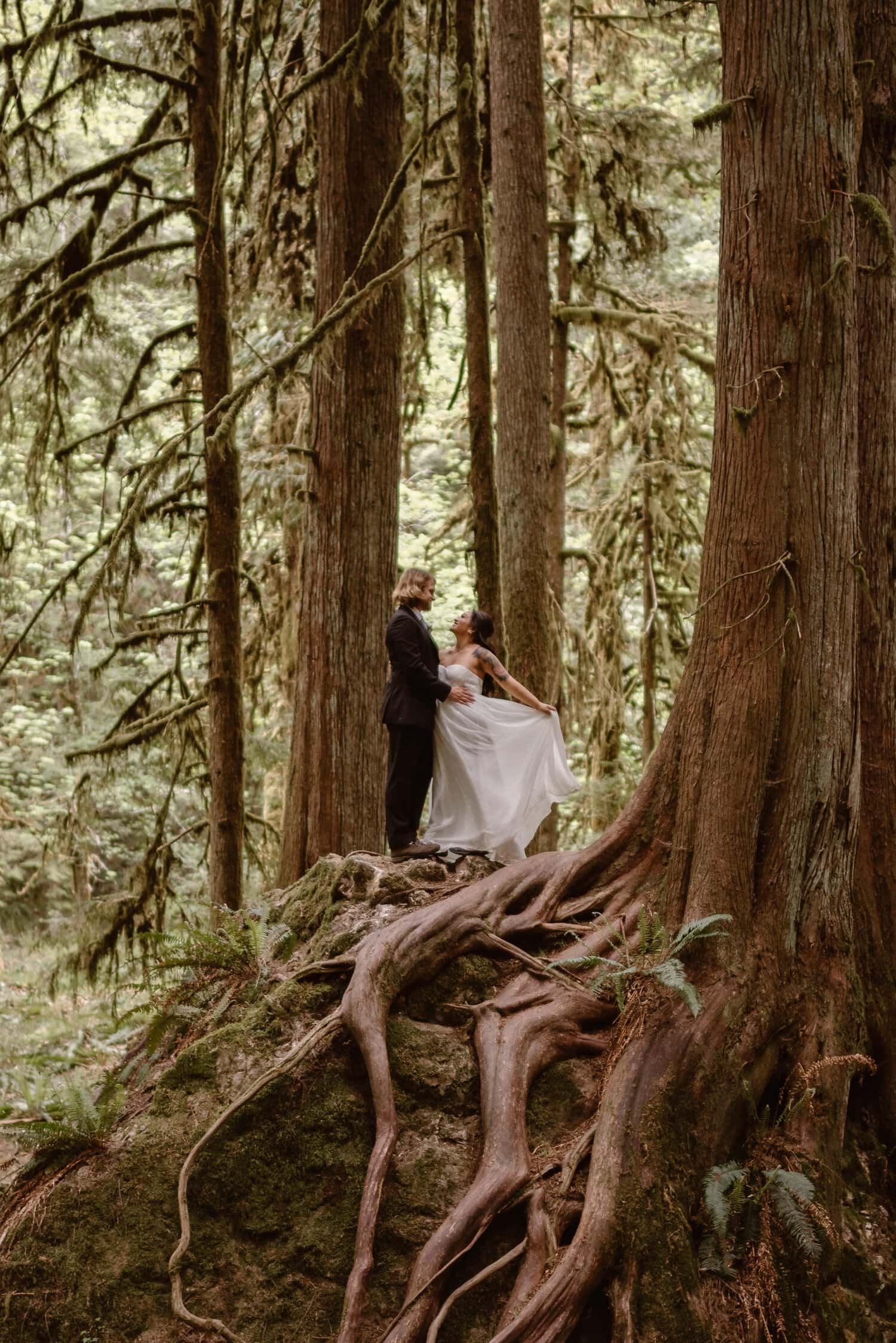 A bride and groom stand in the middle of the forest on their wedding day.