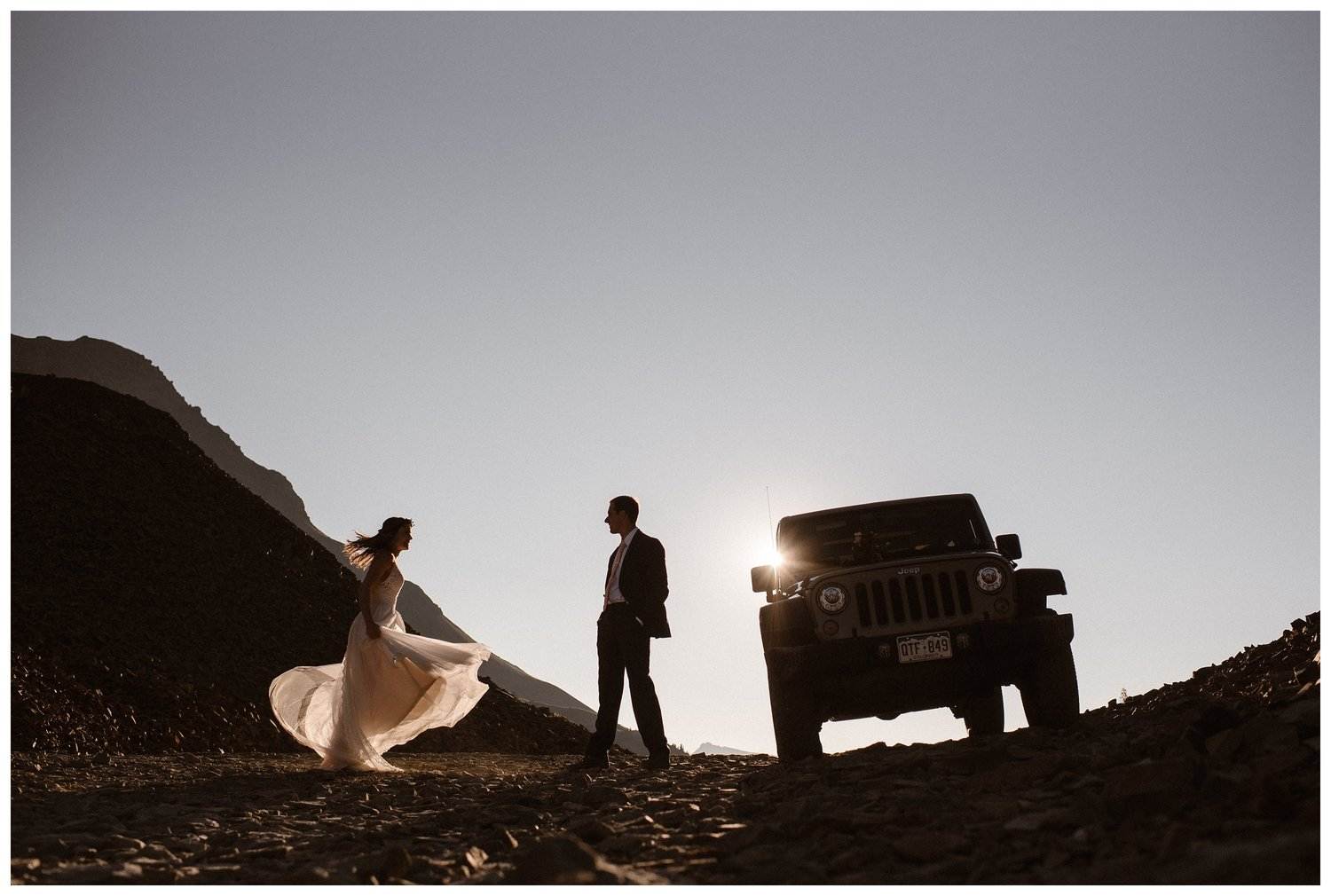 A bride and groom look at each other on a road. There is a jeep beside them on the right.