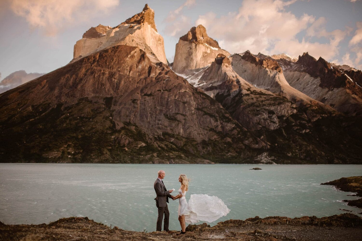 Bride and groom saying their vows in front of a mountain.