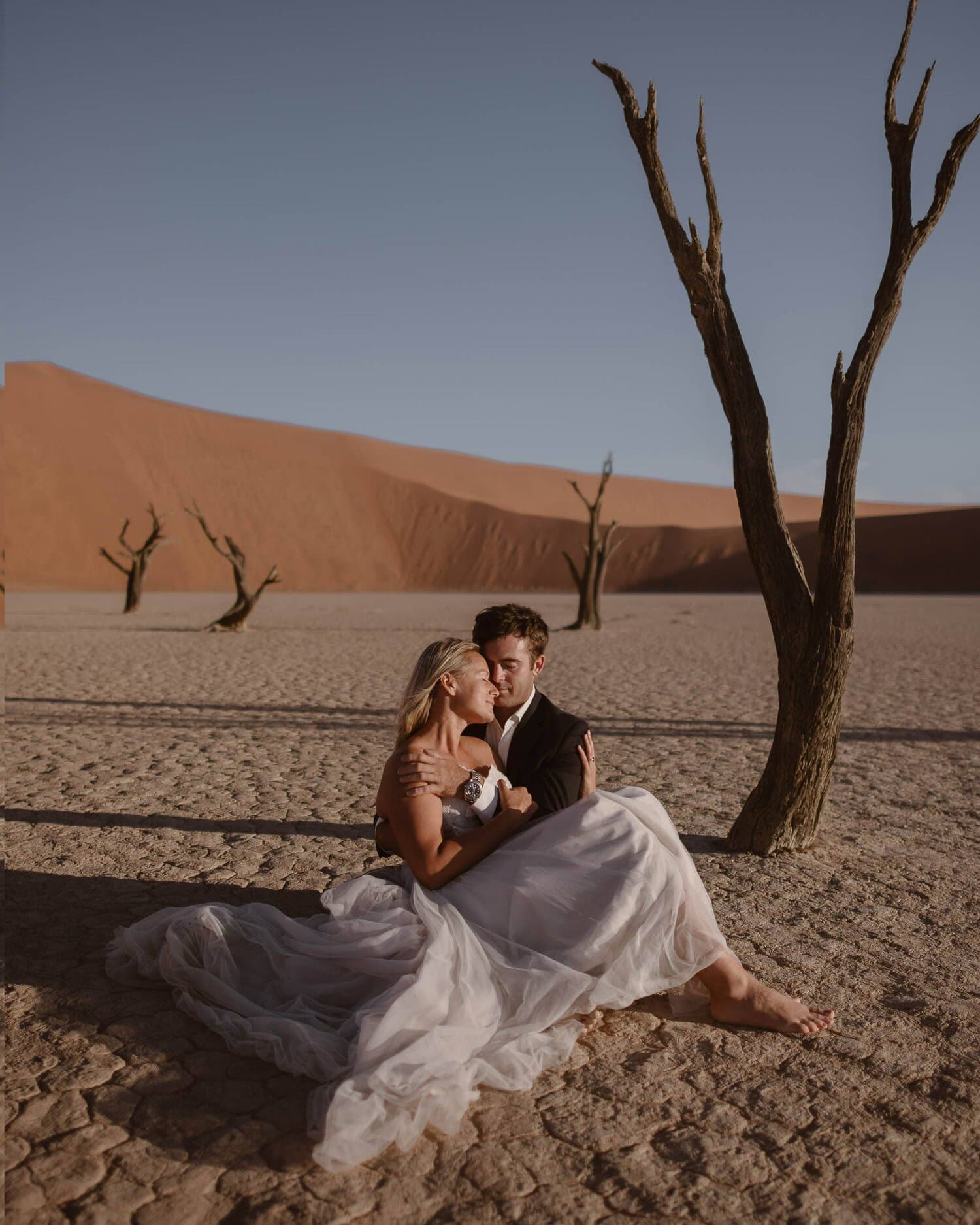 Bride and groom embrace in a desert.