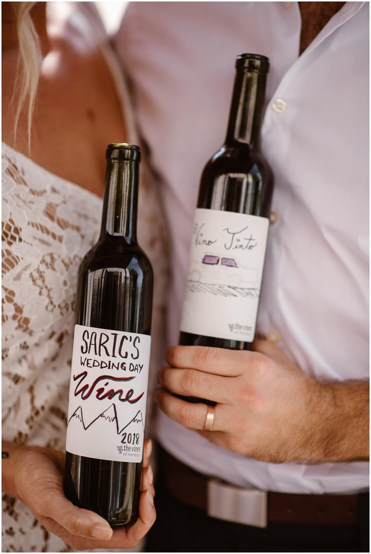A couple hold bottles of wine on their wedding day.