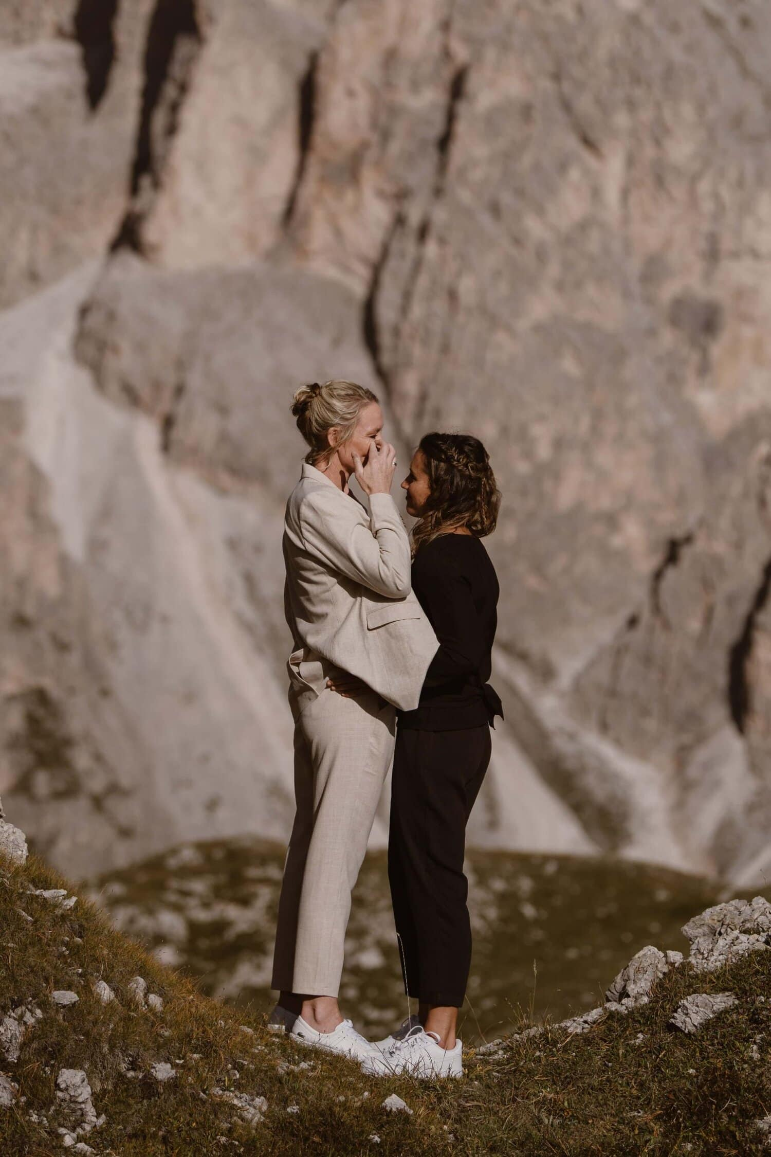 Two brides embracing in the Italian Dolomites.