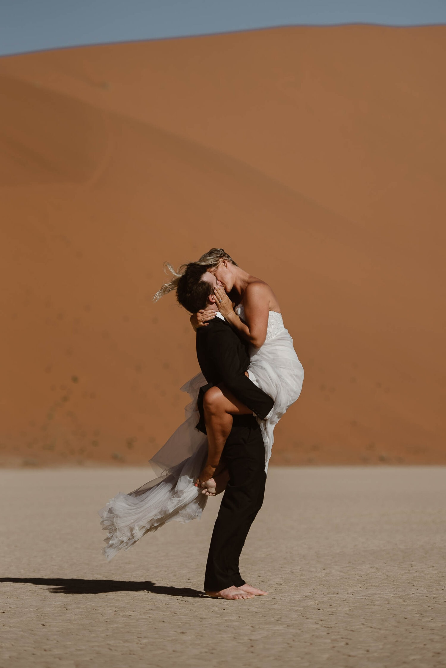 Bride and groom kiss in a desert.