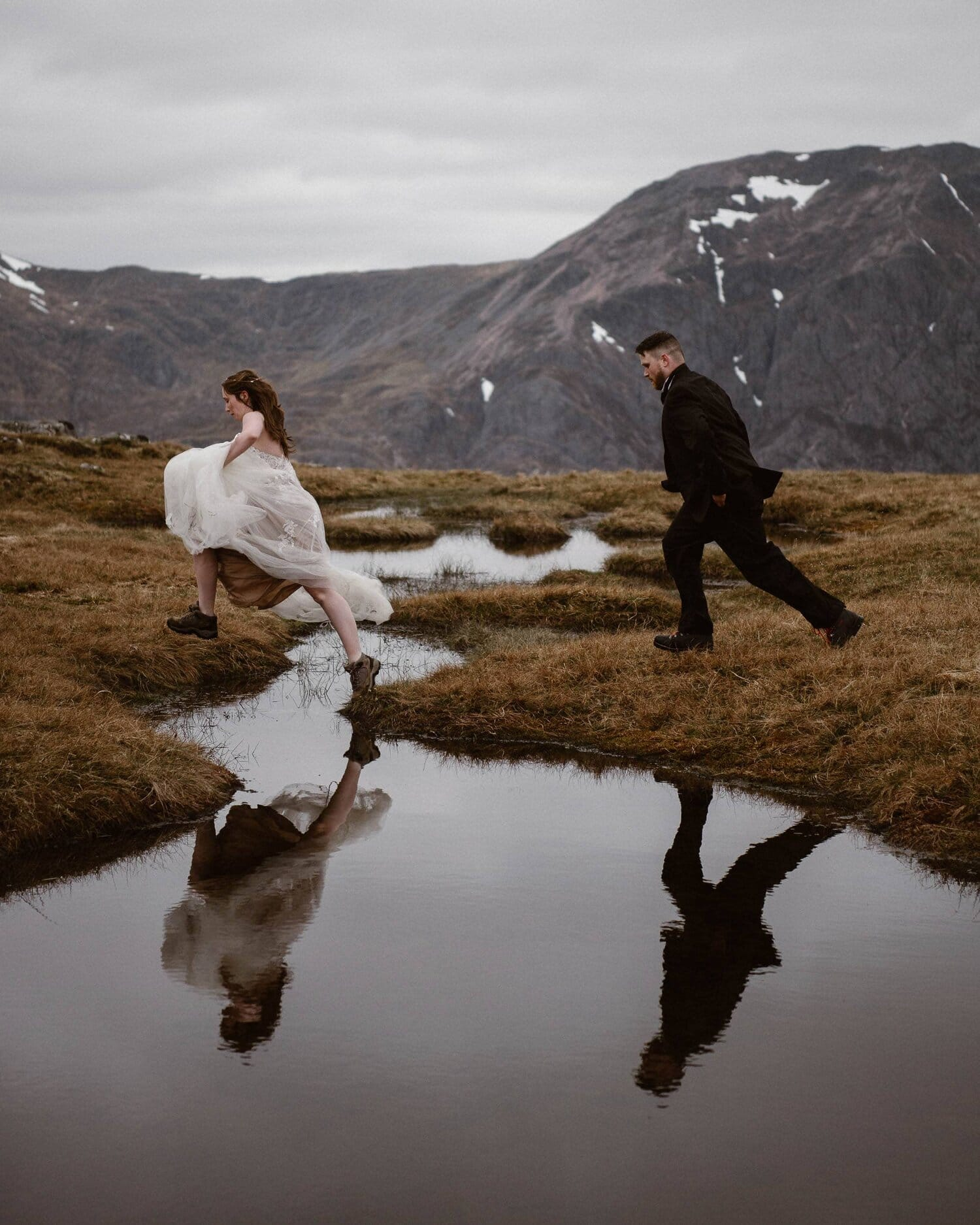 Bride and groom leap over a stream on their wedding day.