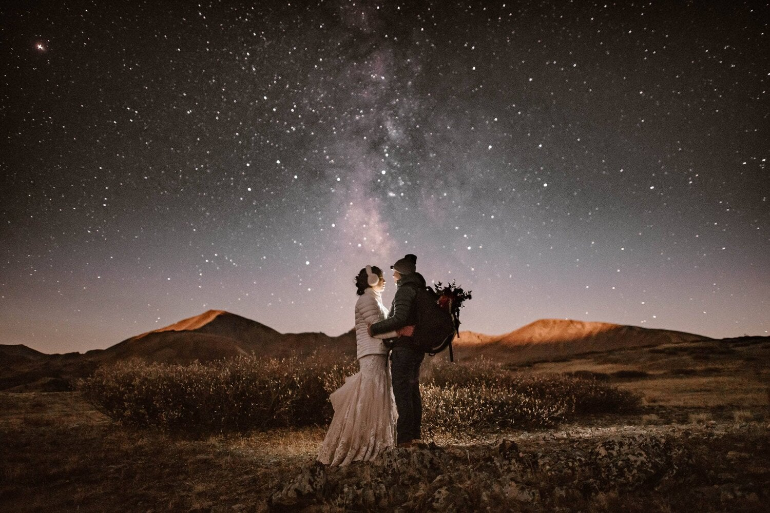 Bride and groom embrace while watching the starry night sky.