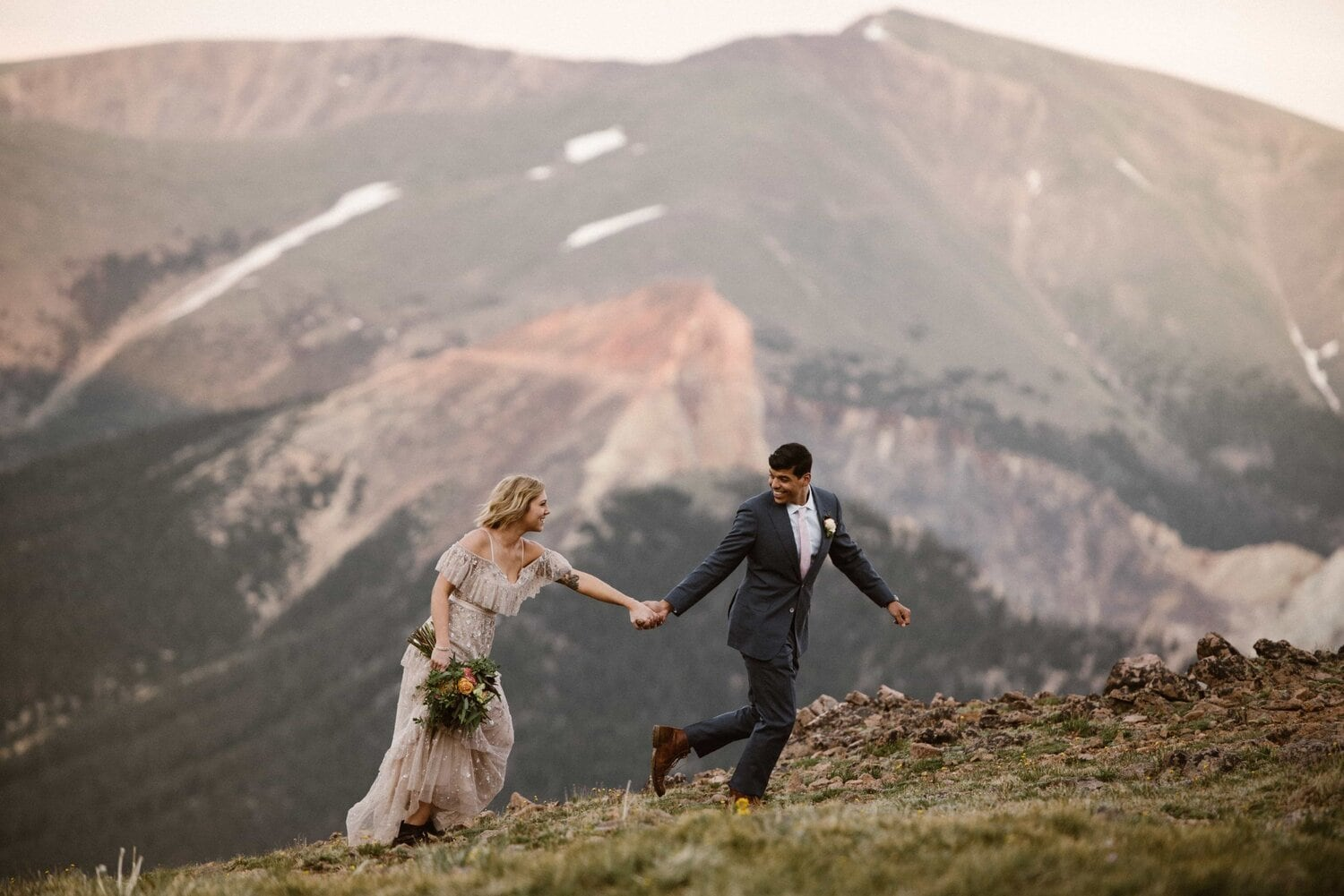 Bride and groom are hand in hand while walking on a mountain.