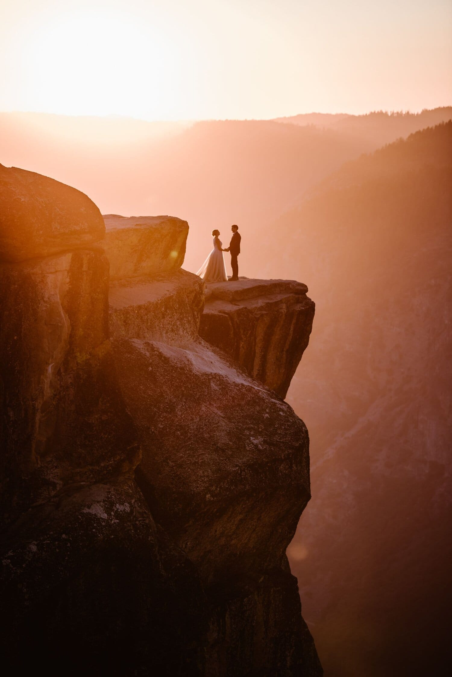 Bride and groom hold hands during sunset at the edge of a cliff.