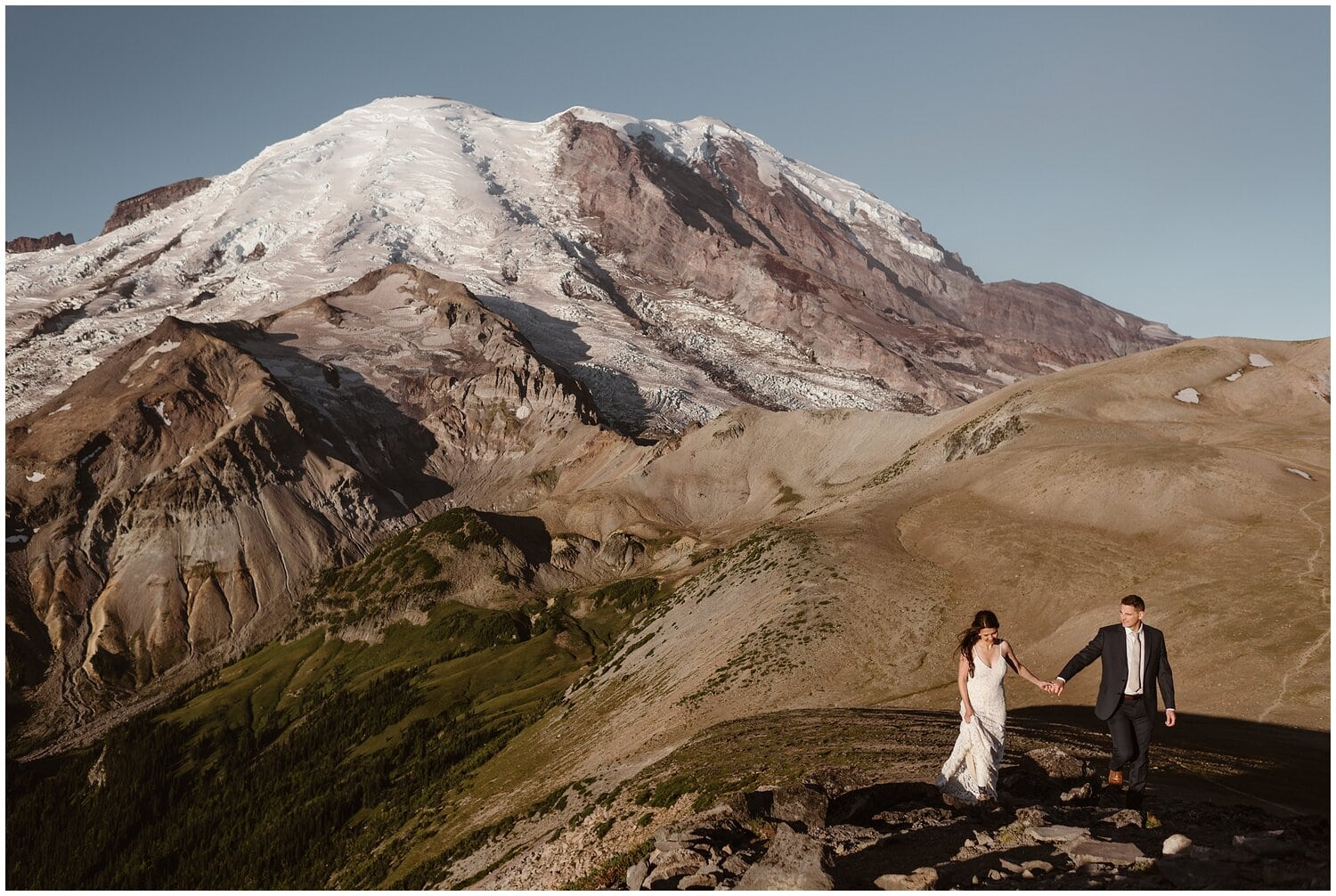 A bride and groom walk in the mountains on their wedding day.
