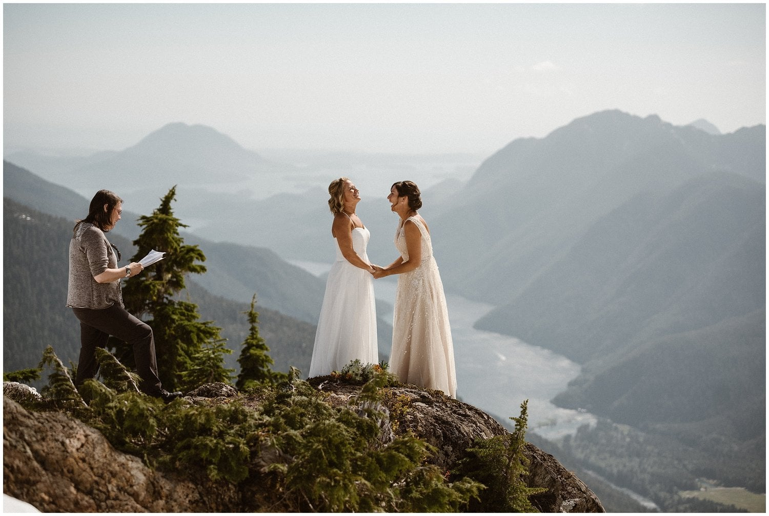Two brides laugh while holding hands during their elopement ceremony.