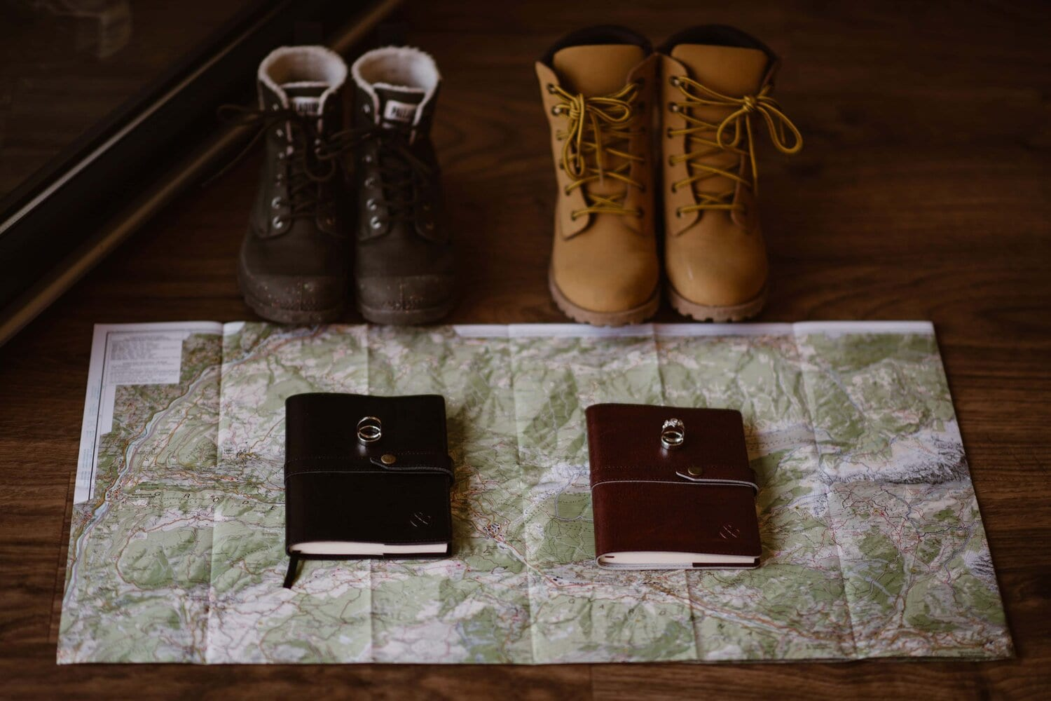A close-up of two pairs of boots next to two vow books which sit on a map of the Italian Dolomites. There are wedding rings on top of the two vow books.