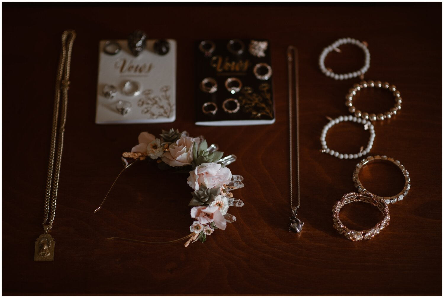 Details for a wedding on a table including a headband, necklaces rings, and vow books.