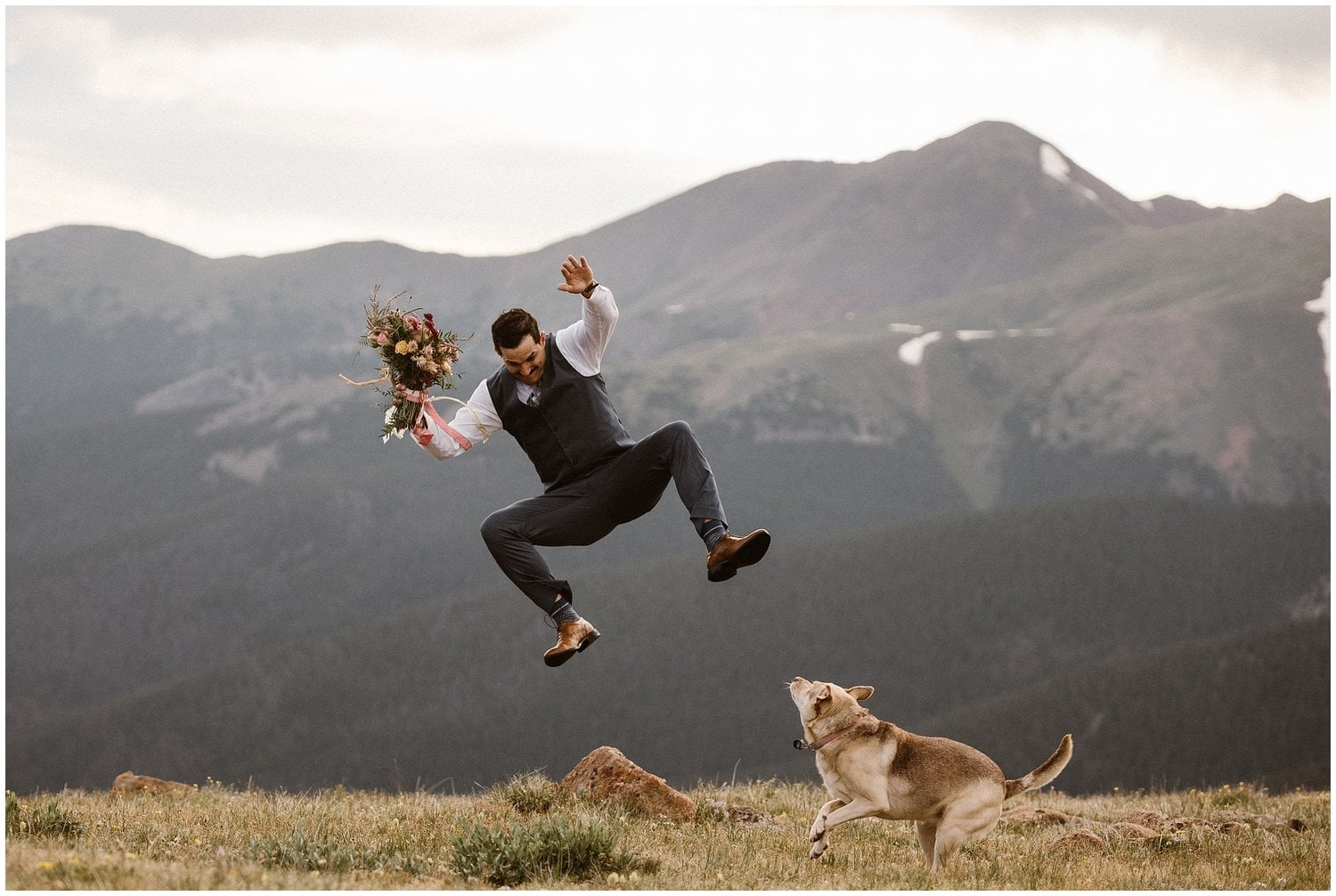 A groom jumps in mid-air while a dog runs on the ground underneath him.