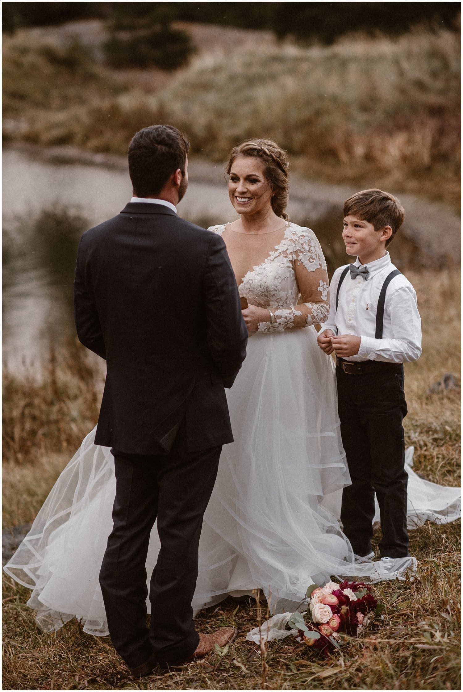 Bride and groom smile at each other with their son standing by their side.