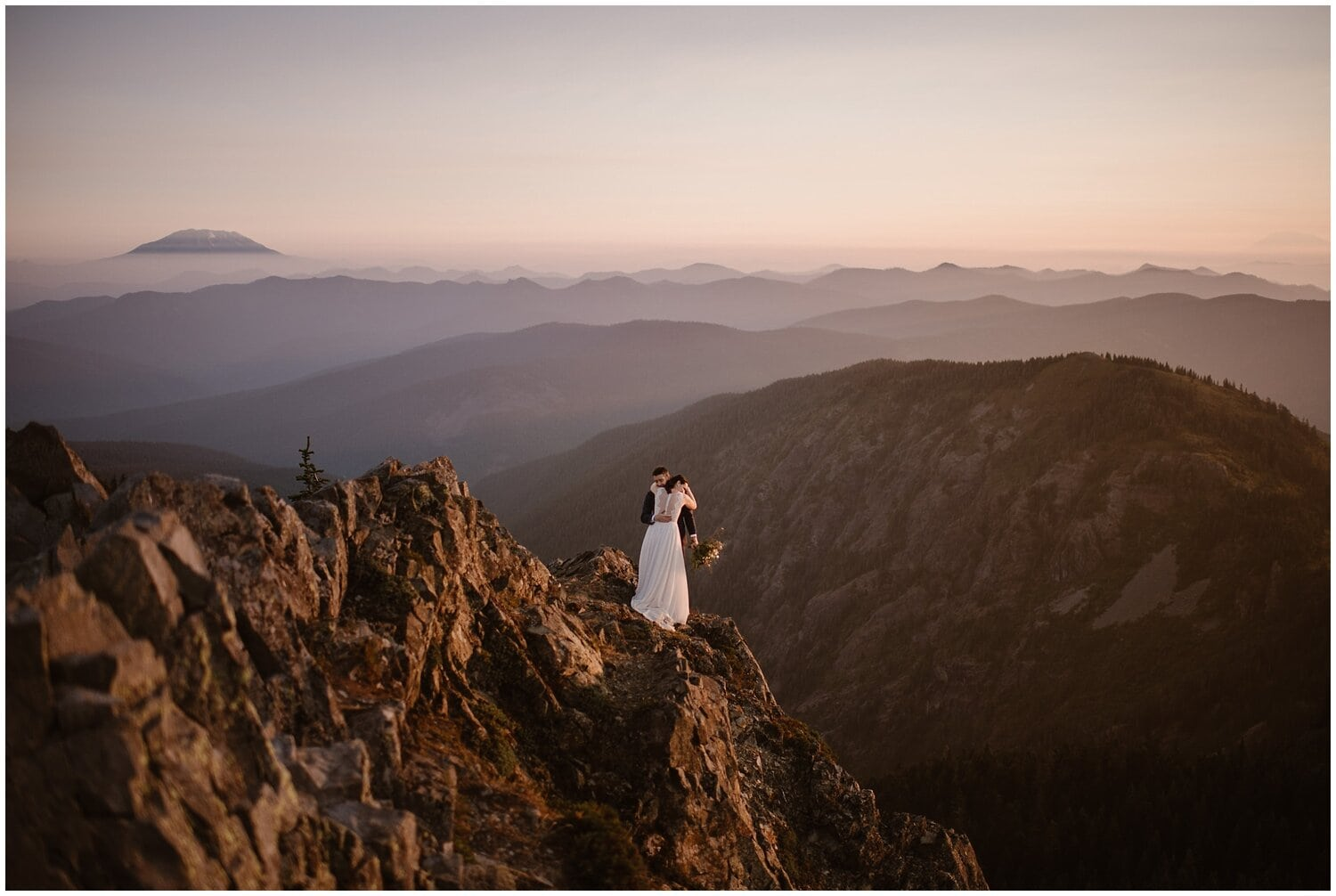 Bride and groom stand on a mountain on their wedding day.
