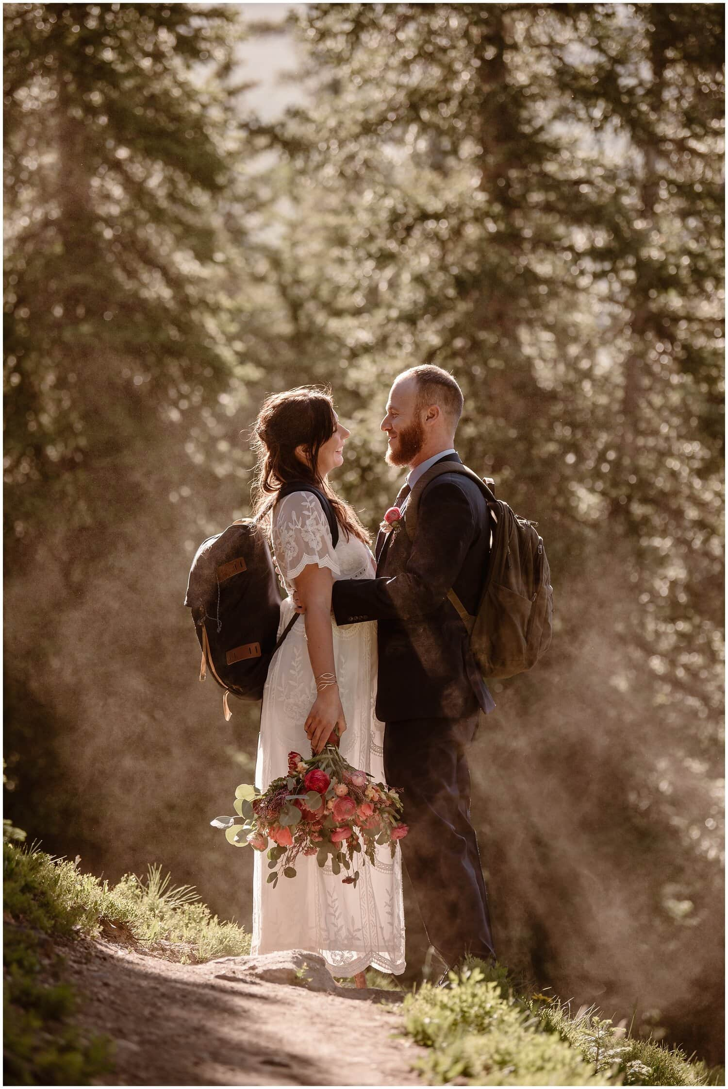 A bride and groom smile at each other while wearing backpacks in a forest. The bride carries a bouquet of flowers.