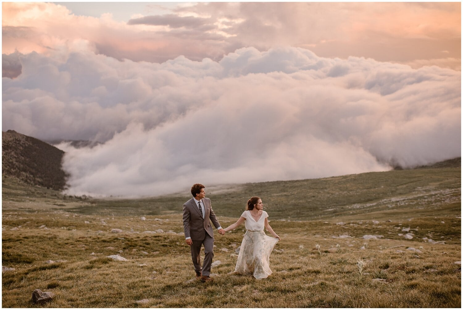 A bride and groom walk through a meadow on their wedding day with a cloud inversion behind them.