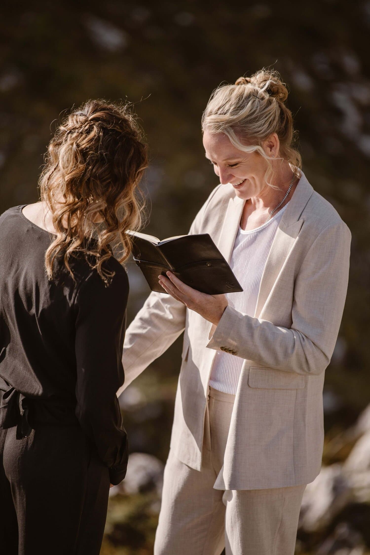Two brides reading vows during their wedding ceremony in the Italian Dolomites.