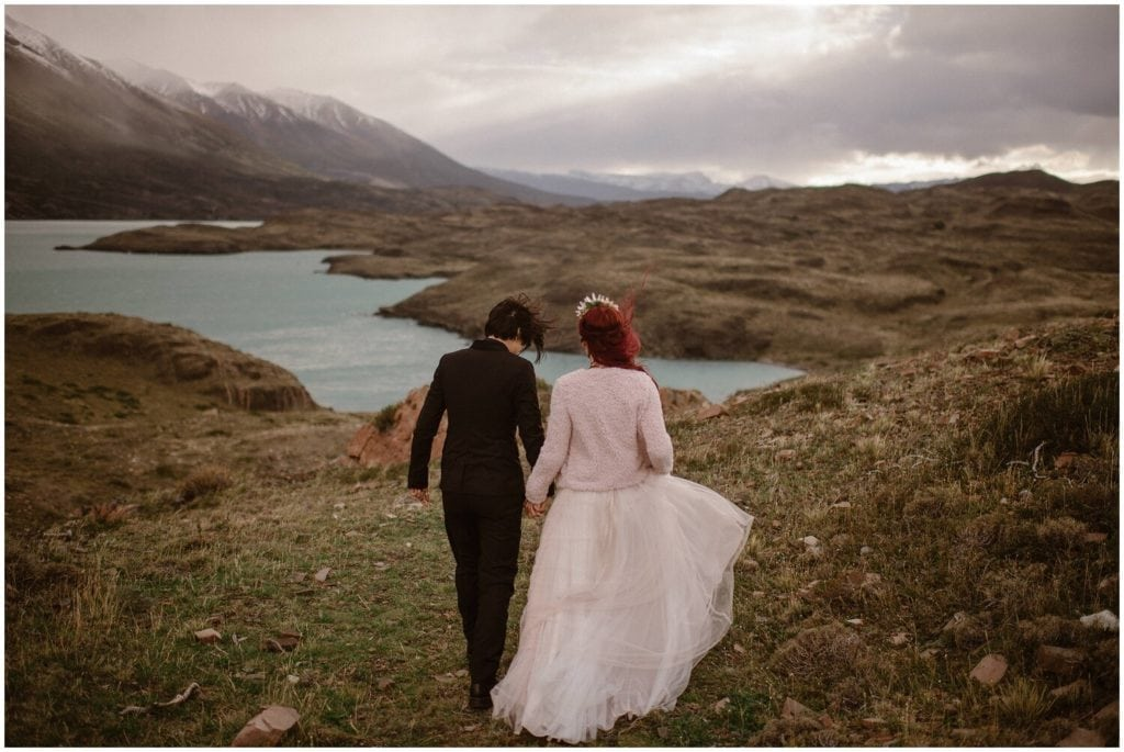 A couple hold hands on their wedding day in Patagonia.