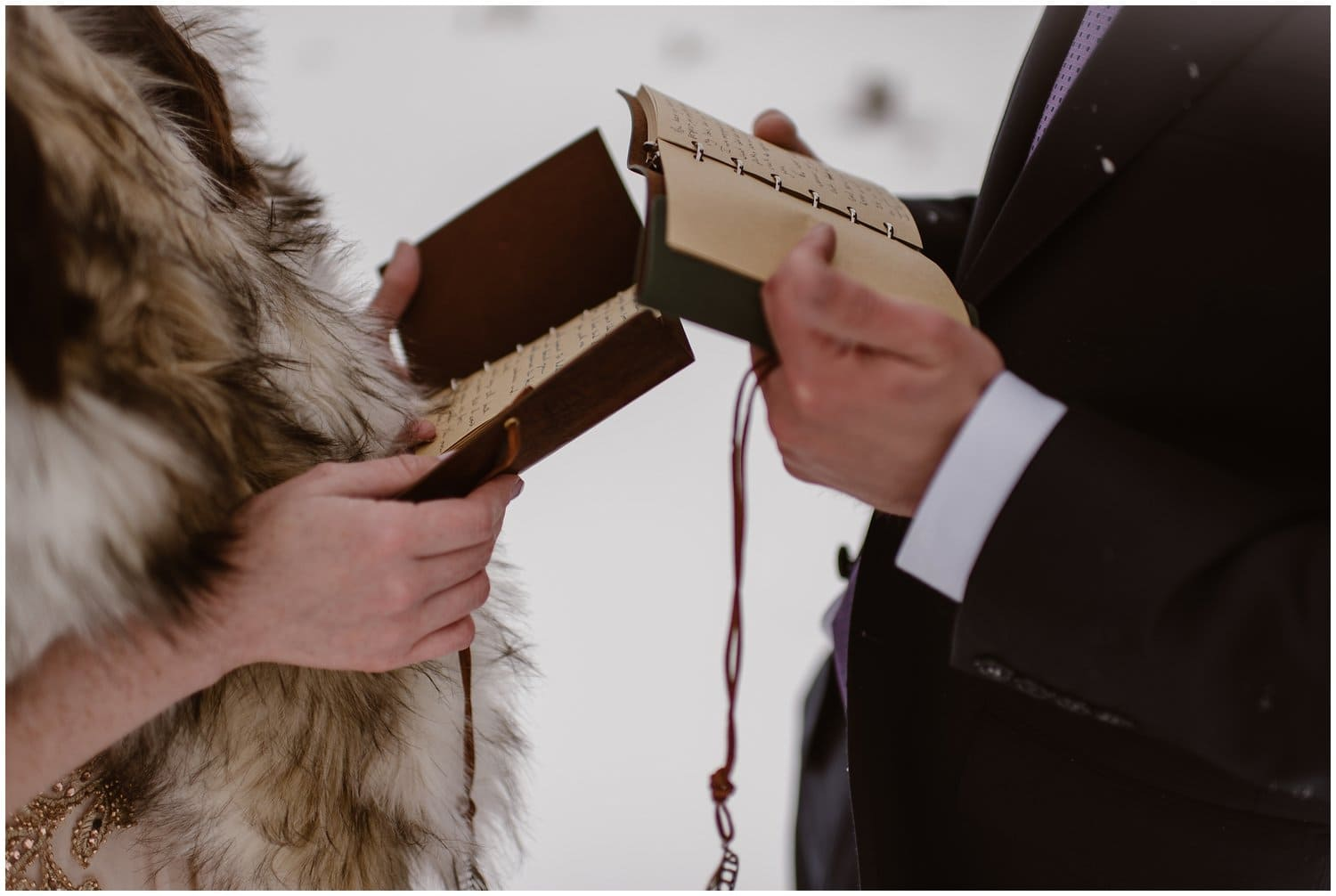 Close-up of a bride and a groom holding their vow books.