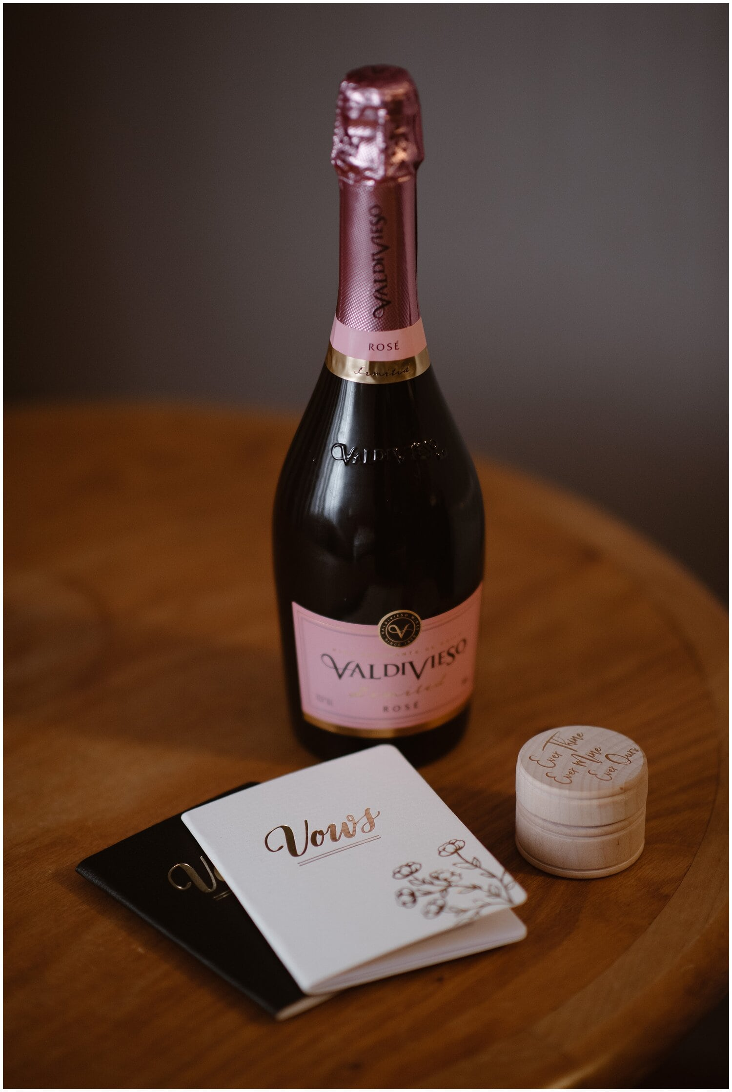 Bottle of champagne next to vow books.
