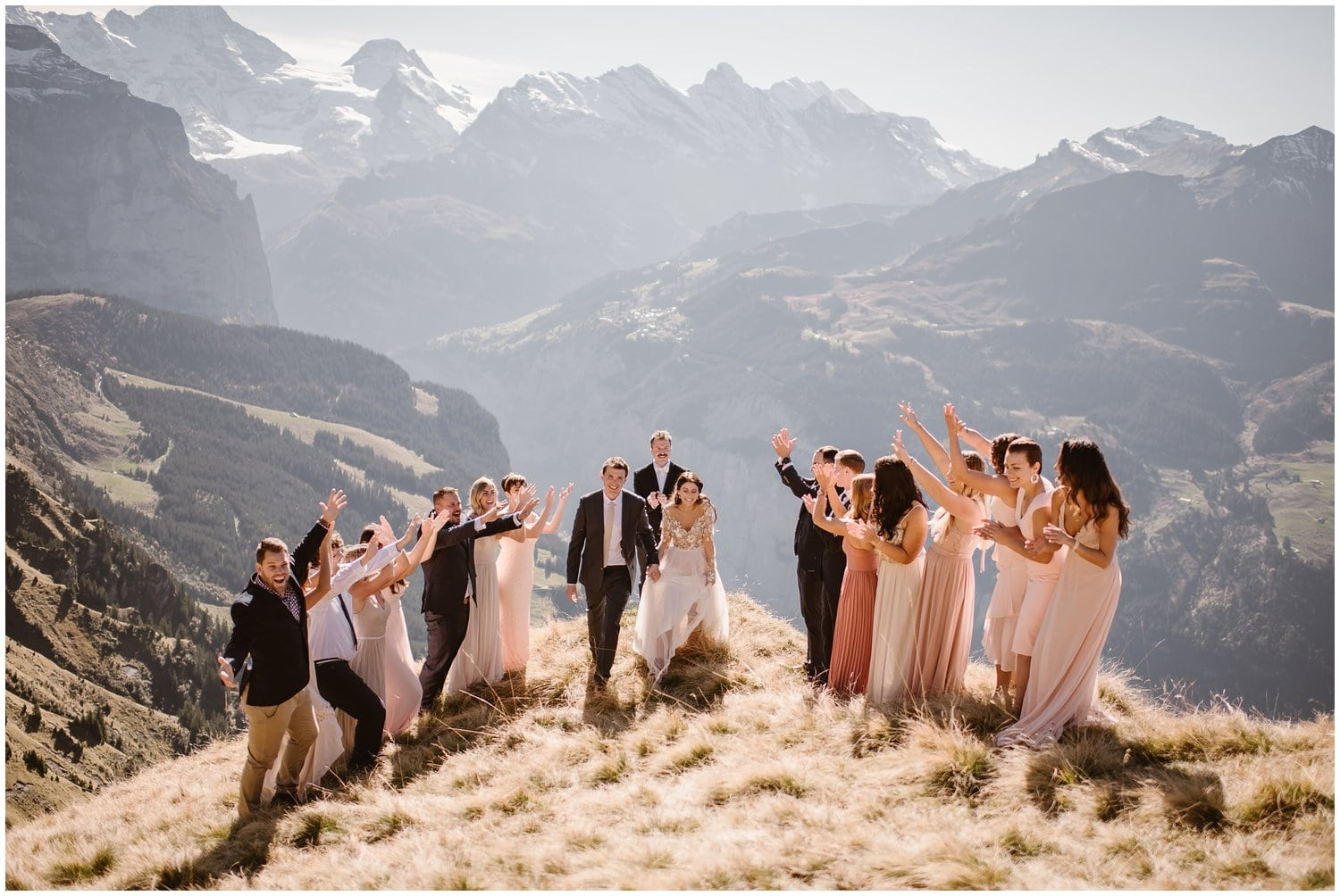A bride and groom finish their wedding ceremony while family cheer them on in the mountains.