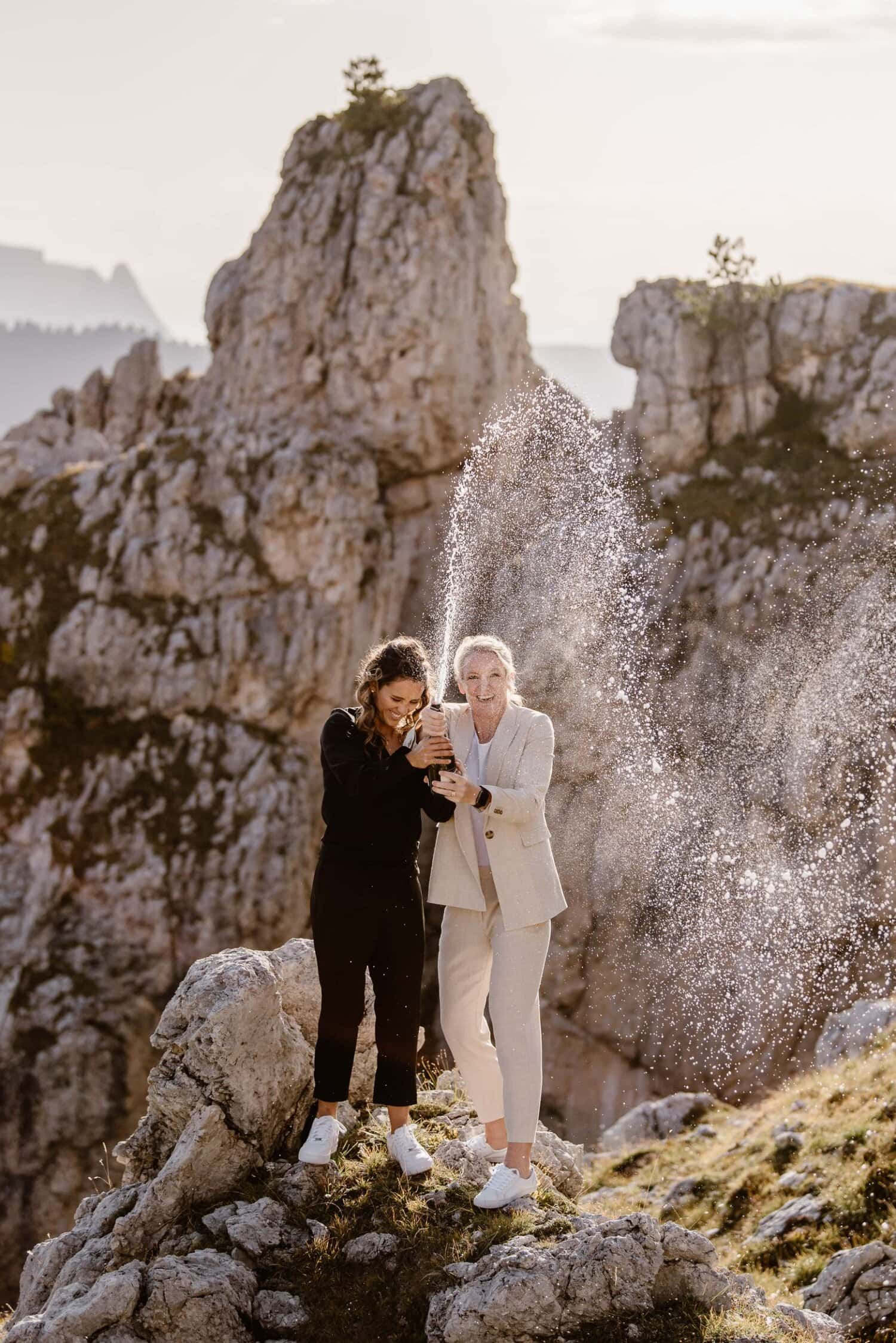 Two brides pop a bottle of champagne in the Italian Dolomites.