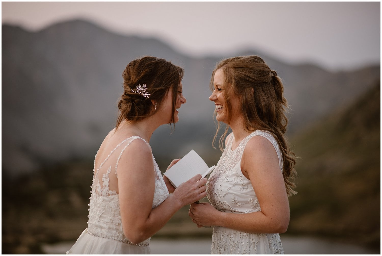 Two brides laugh during their elopement ceremony while one bride holds a vow book.