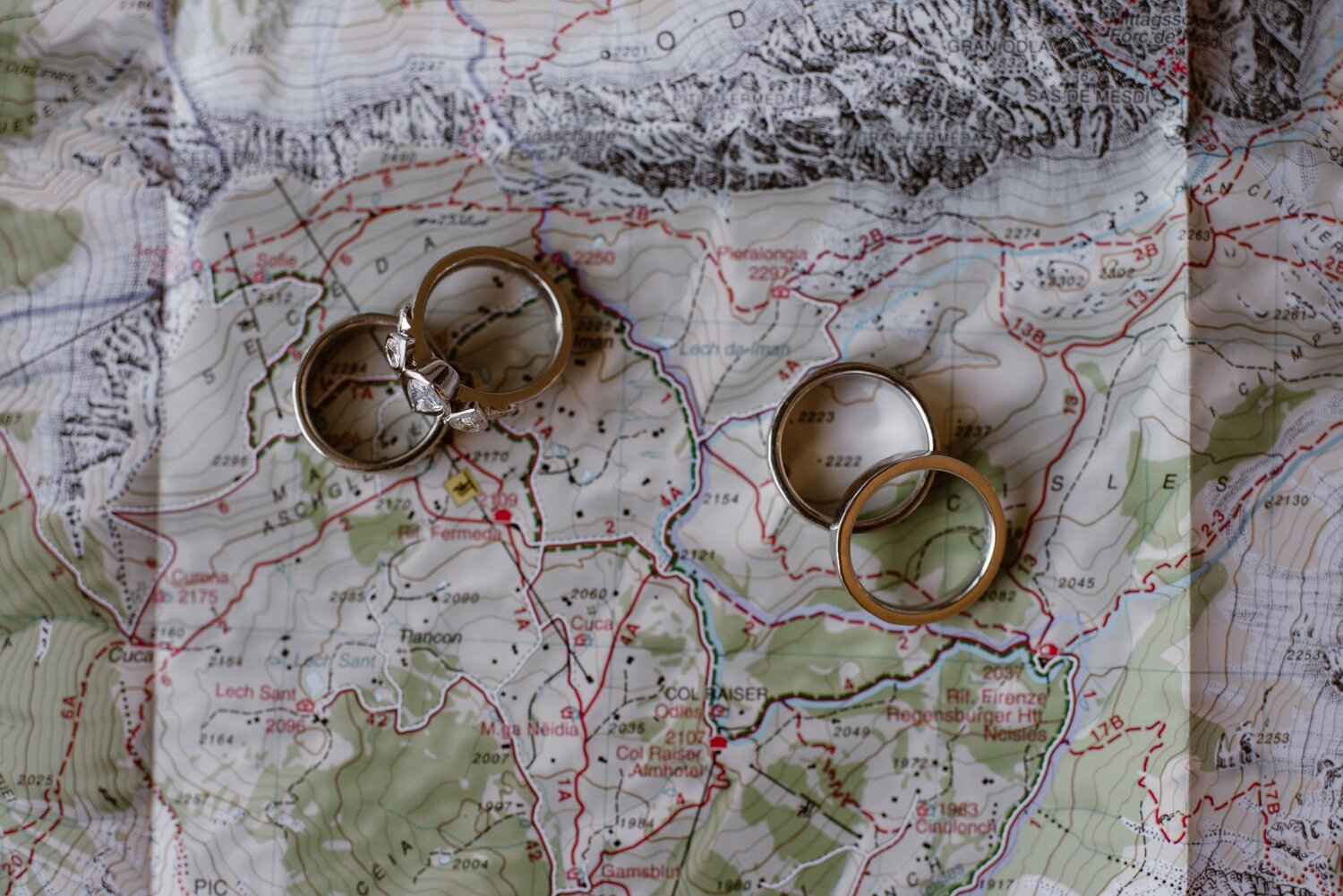 A close-up of wedding bands on top of a map of the Italian Dolomites.