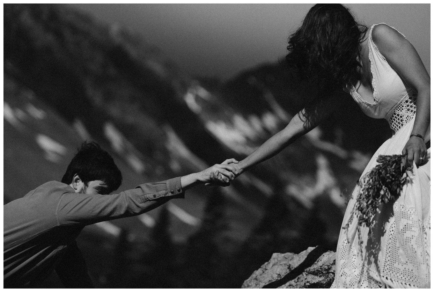 A bride helps a groom climb up as they hold hands. Photo is in black and white.