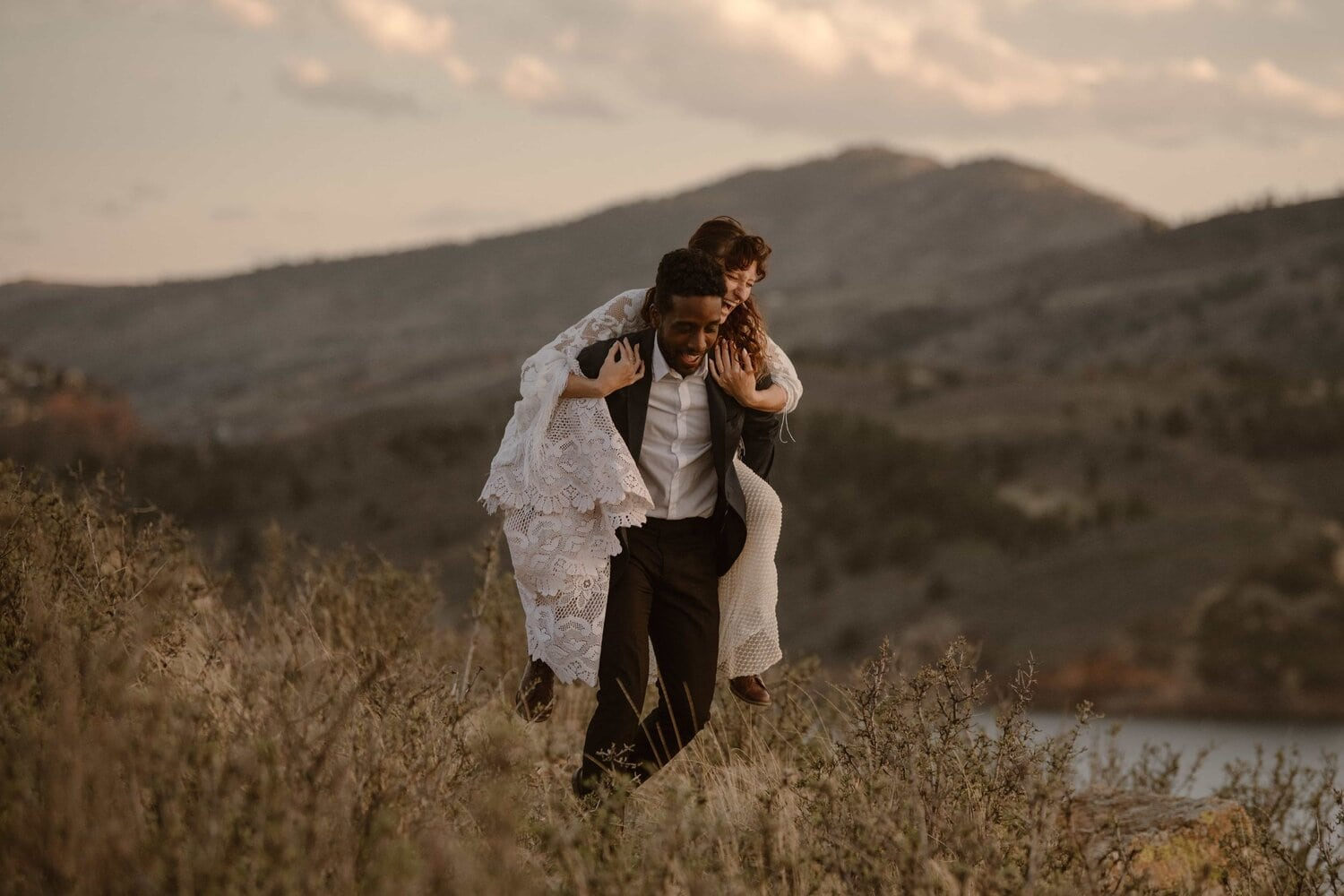 Groom carries bride on his back while walking.