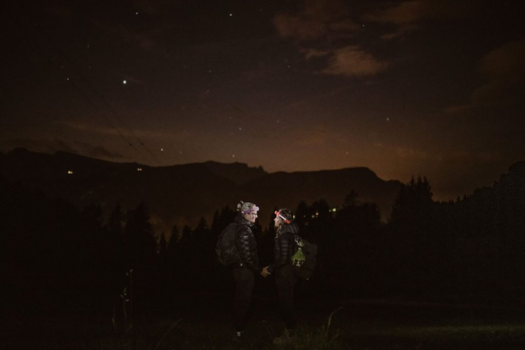 Two brides hold hands in the dark before the sun rises in the Italian Dolomites.