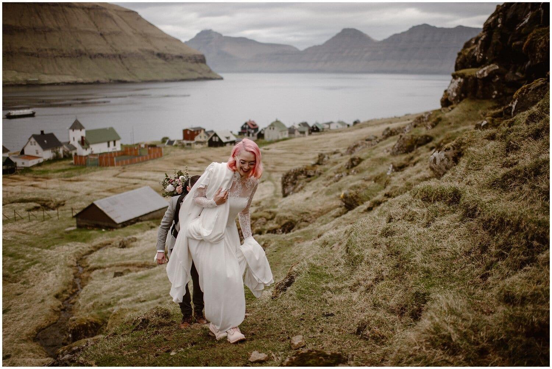 A bride and groom walk up a hill on Faroe Island.