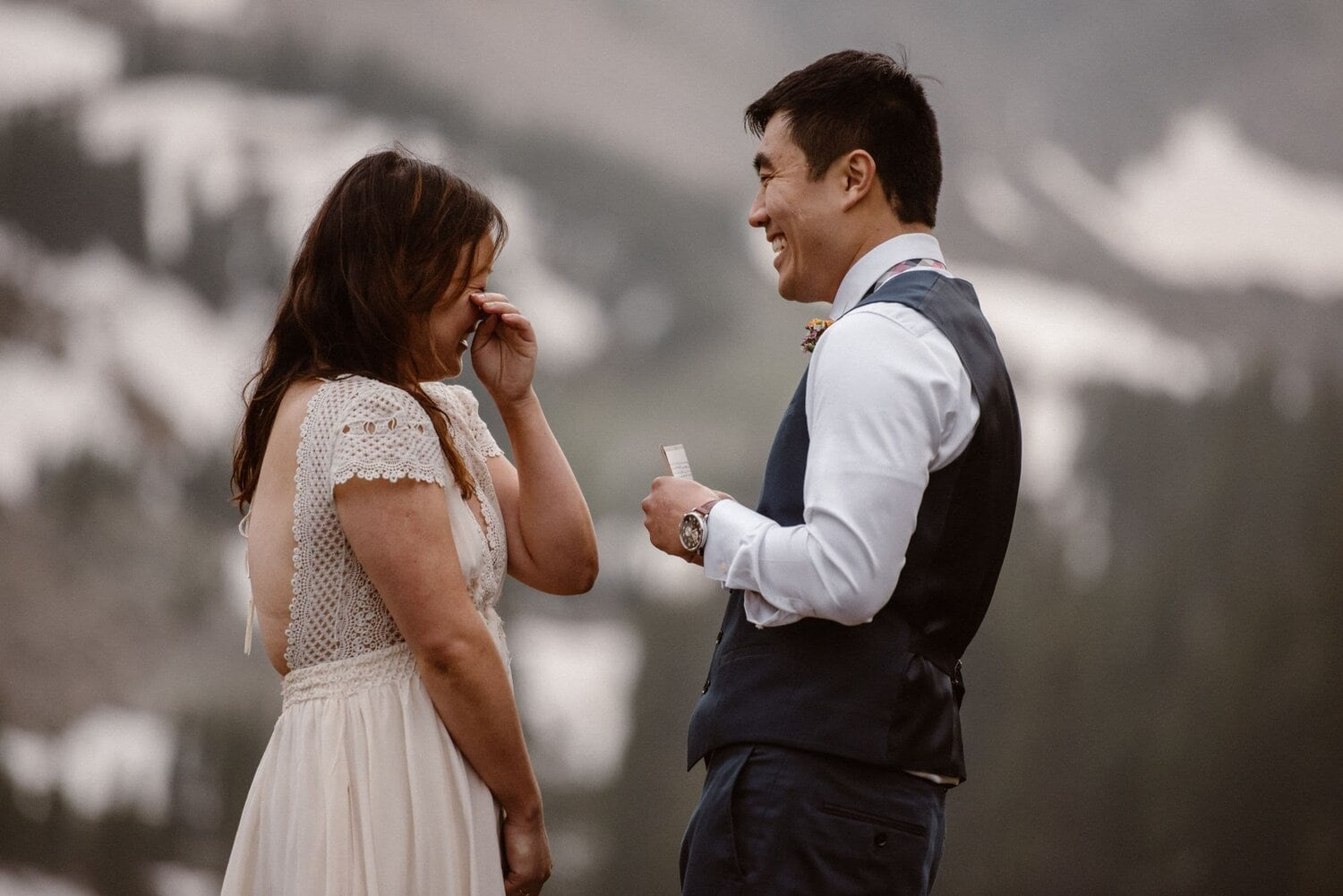 Bride wipes off tear while groom reads vows during their elopement ceremony.