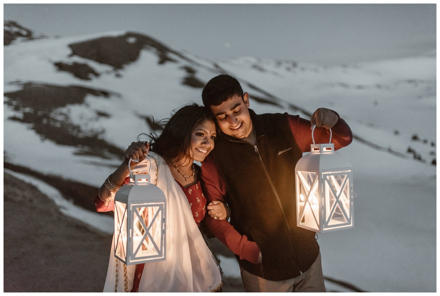 A bride and groom hold lanterns on their elopement day. They are standing with snowy mountains in the back.