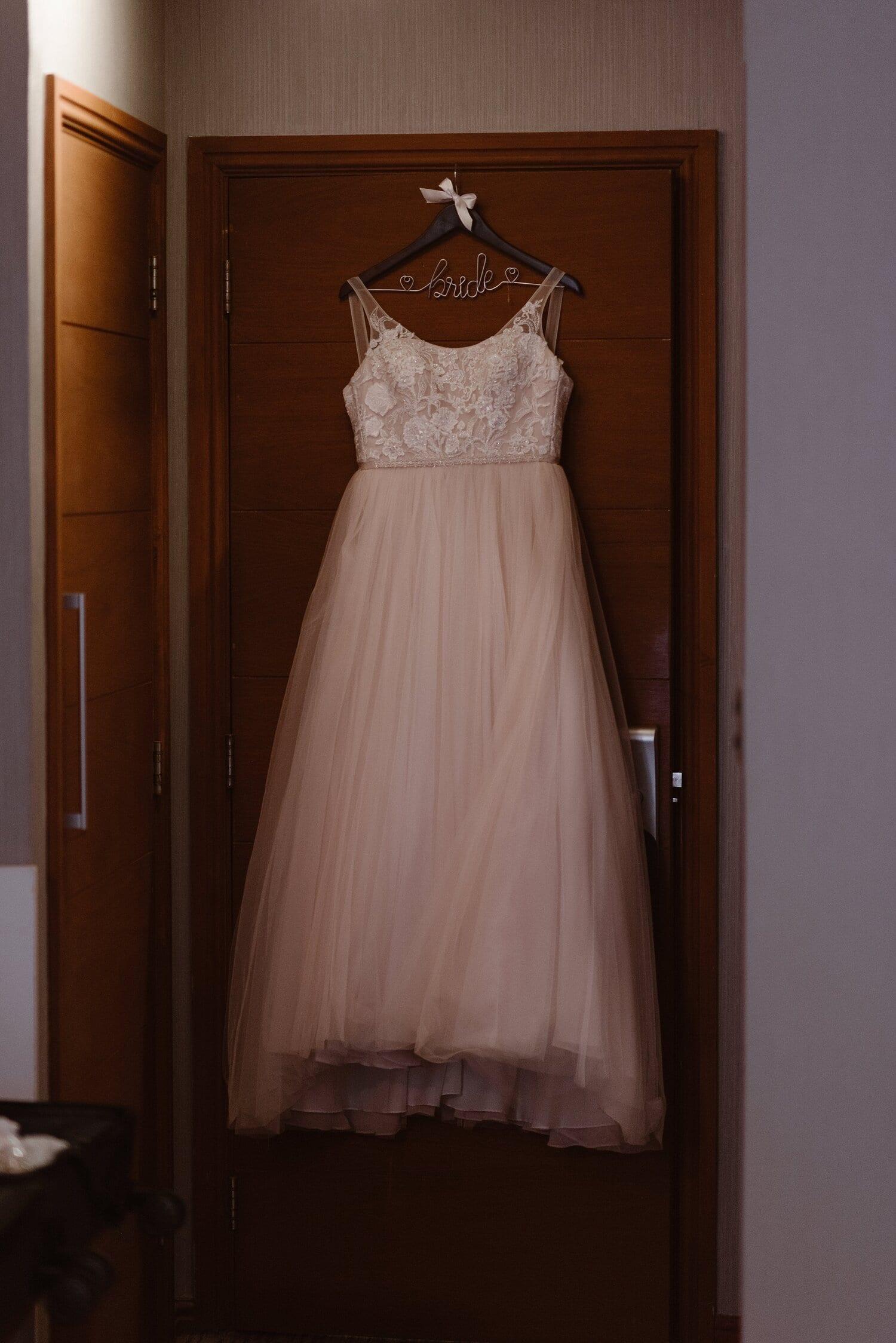 Wedding dress hanging on a door.