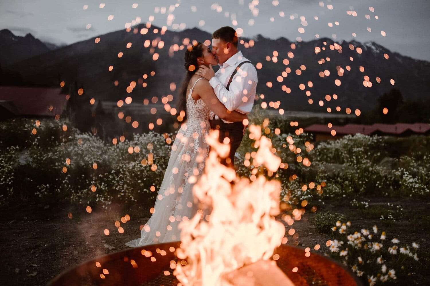 Bride and groom kissing in front of a fire.