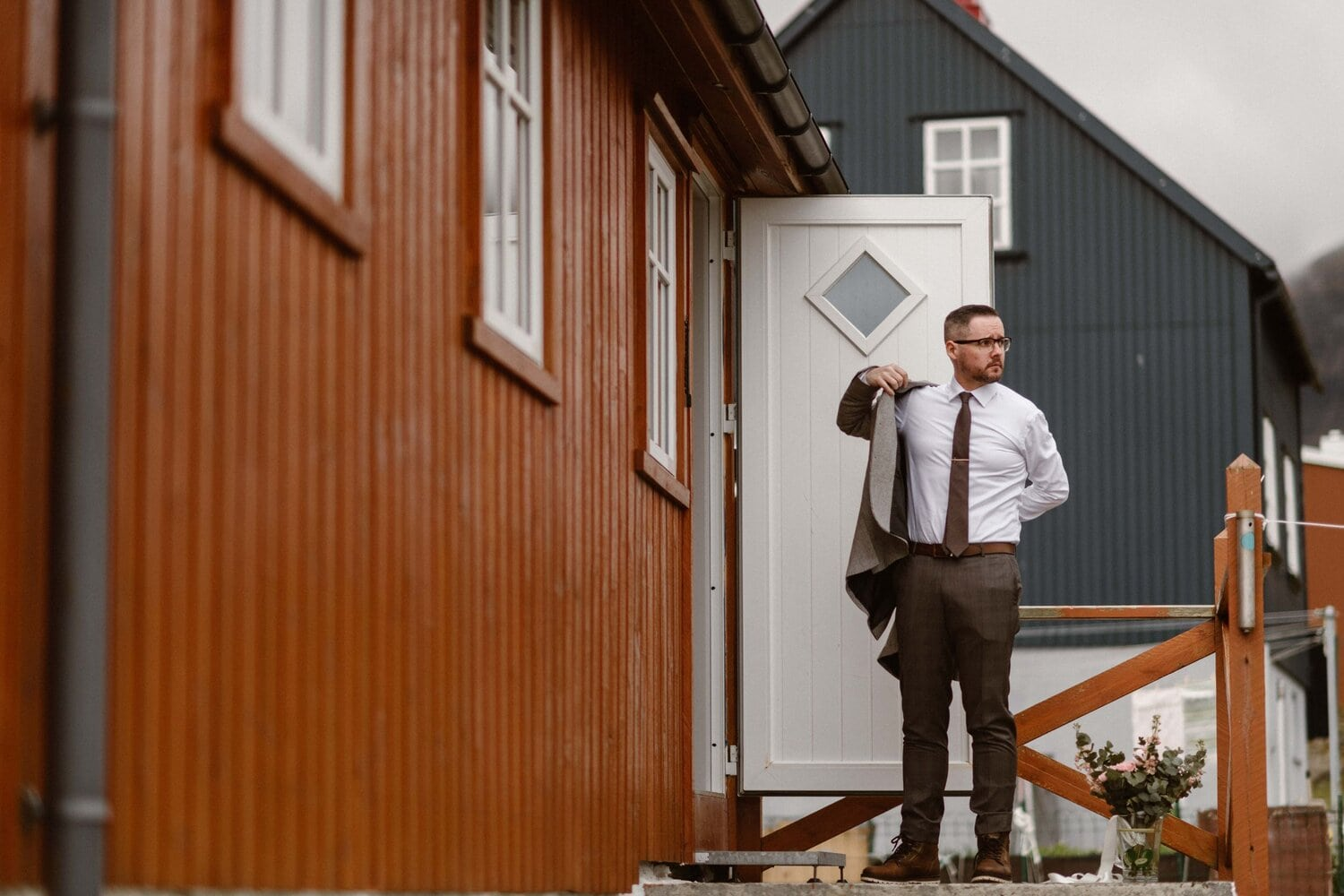 A groom puts on his jacket outside of an Airbnb.