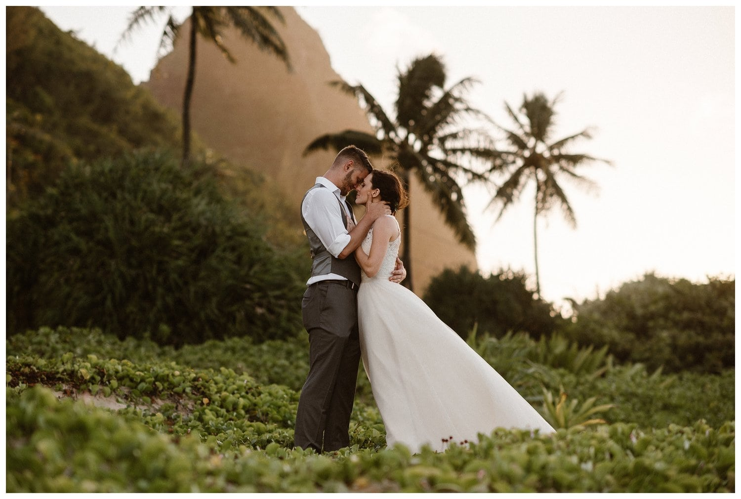 A bride and groom embrace in the middle of greenery with palm trees behind them.