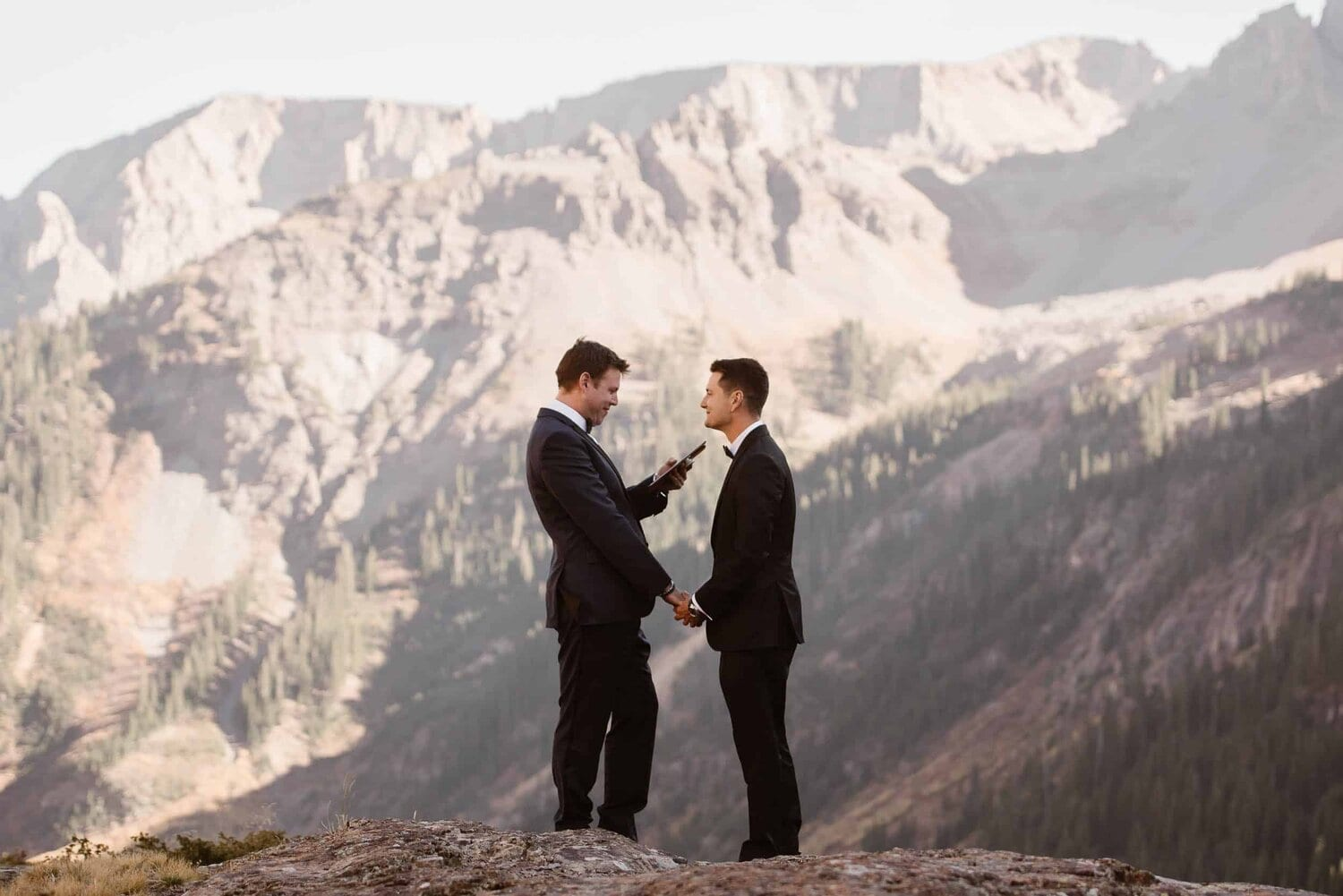 Two grooms say their vows on a mountain top.