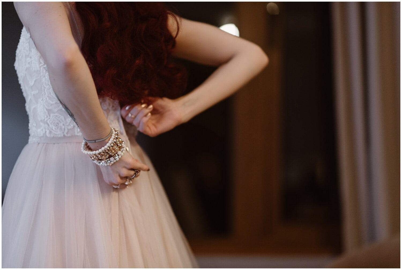 Bride zipping up her wedding dress.