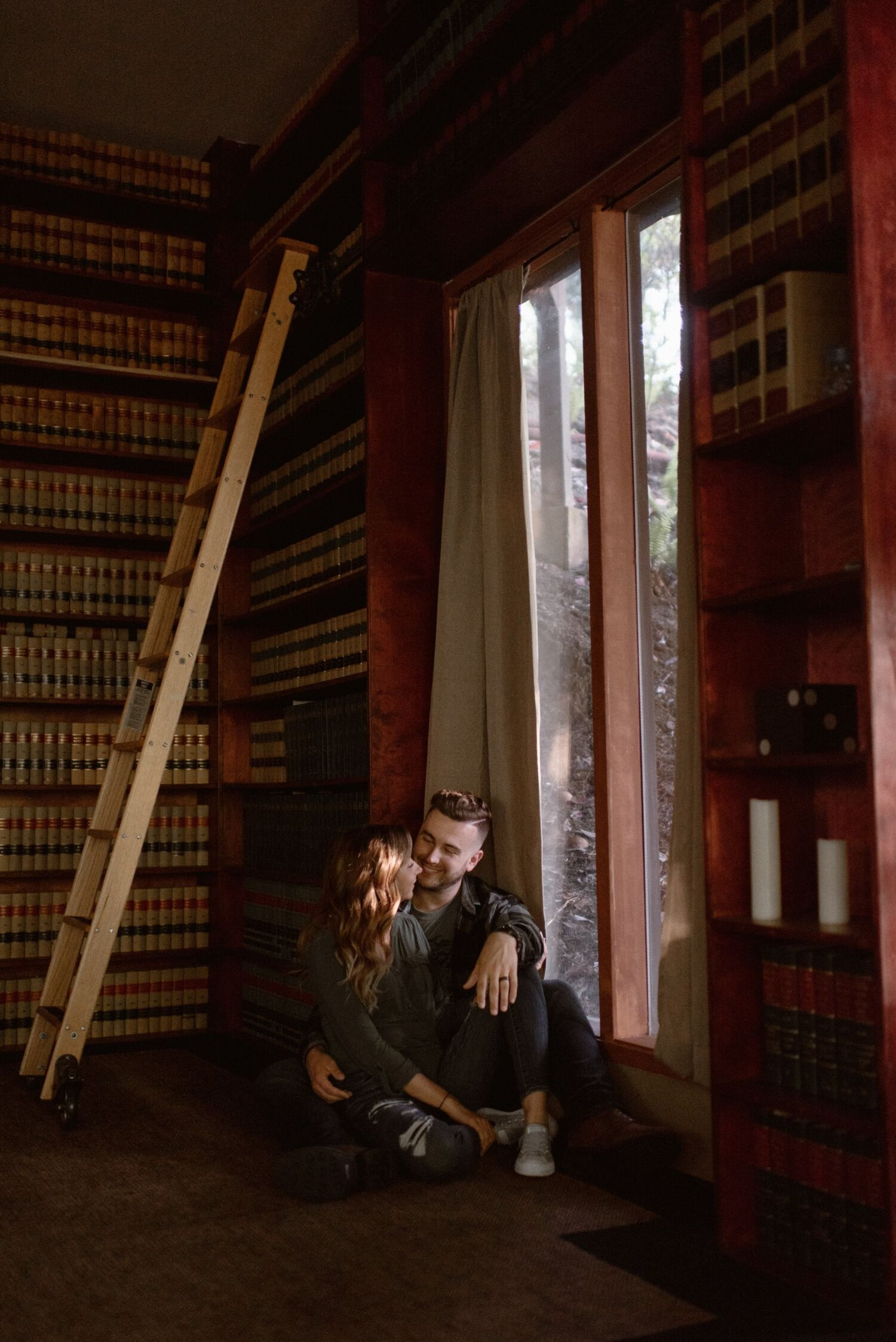 Man and woman embrace in an Airbnb in a room filled with bookshelves.