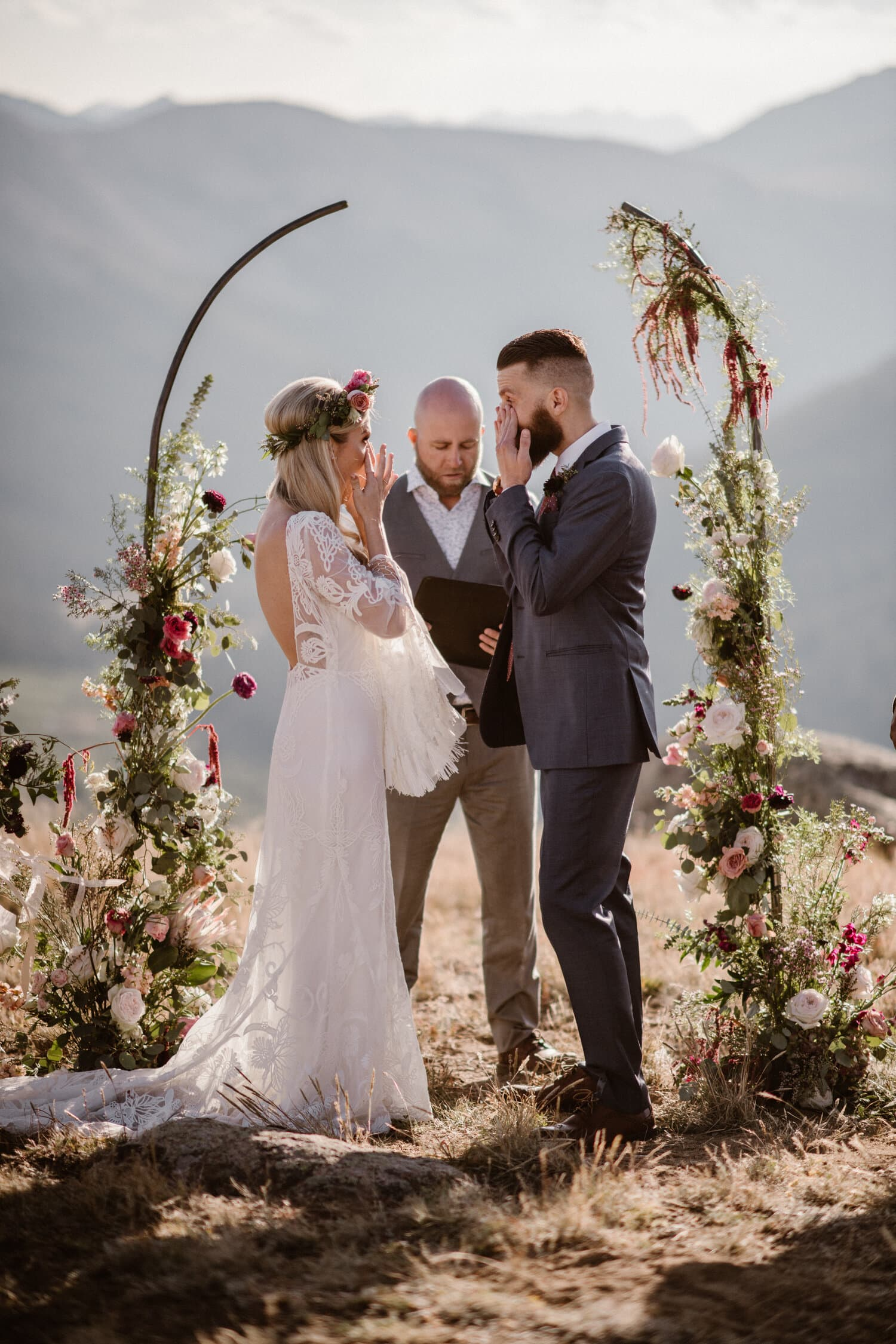 Bride and groom standing in front of a floral arch during their elopement ceremony.