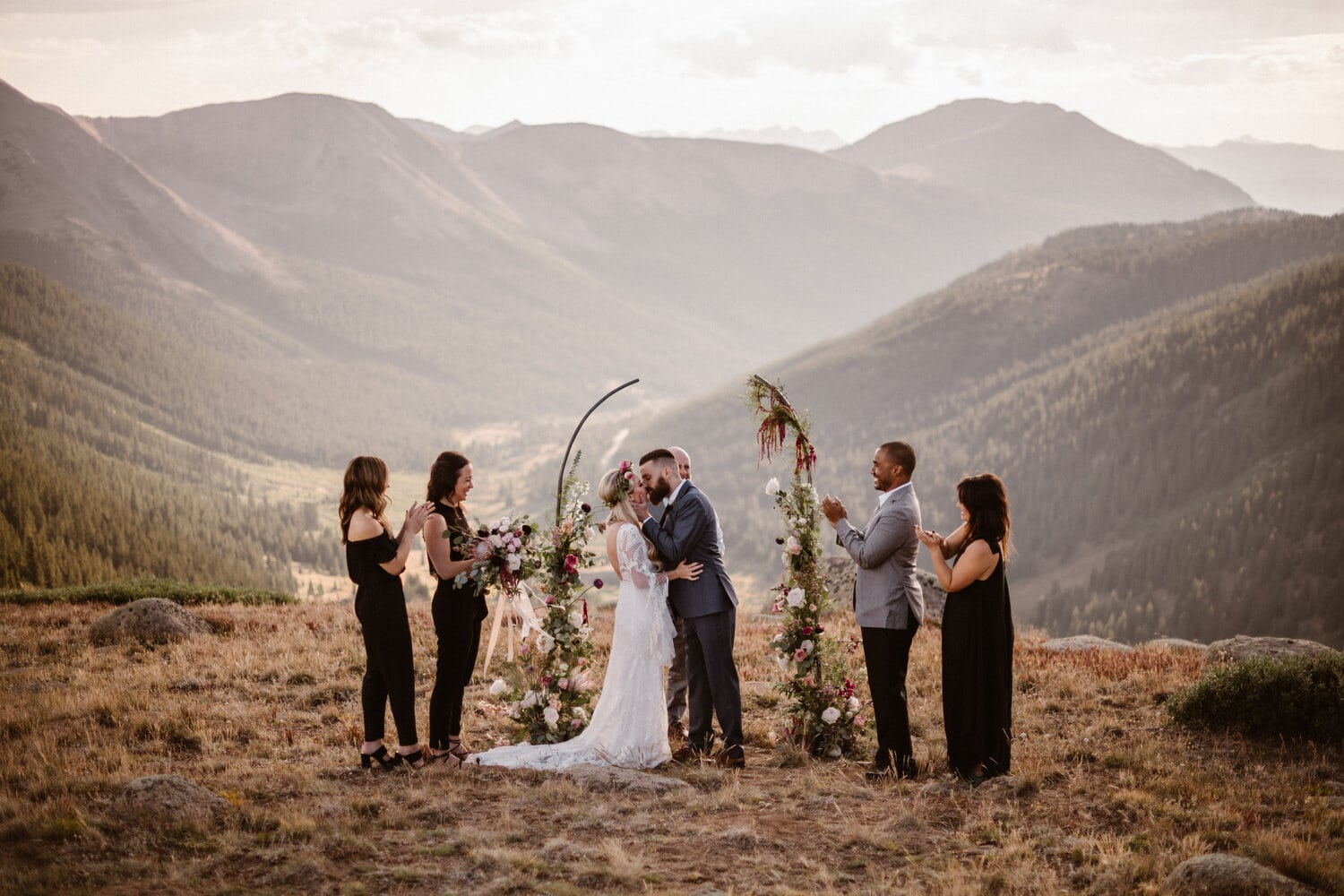 Bride and groom kiss in front of the alter during their ceremony while friends and family stand by their side.