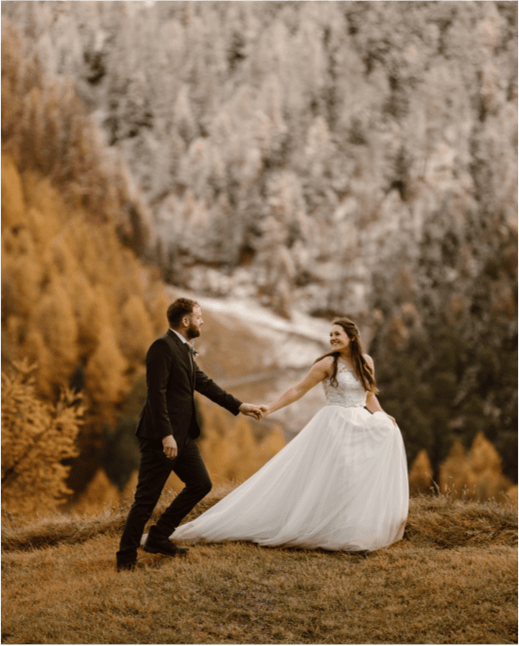 A bride with long brown hair looks back and grabs her grooms hand during their elopement in Colorado.